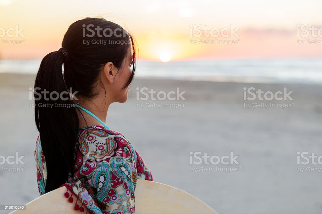 Thoughtful woman watches the sun set over the ocean stock photo