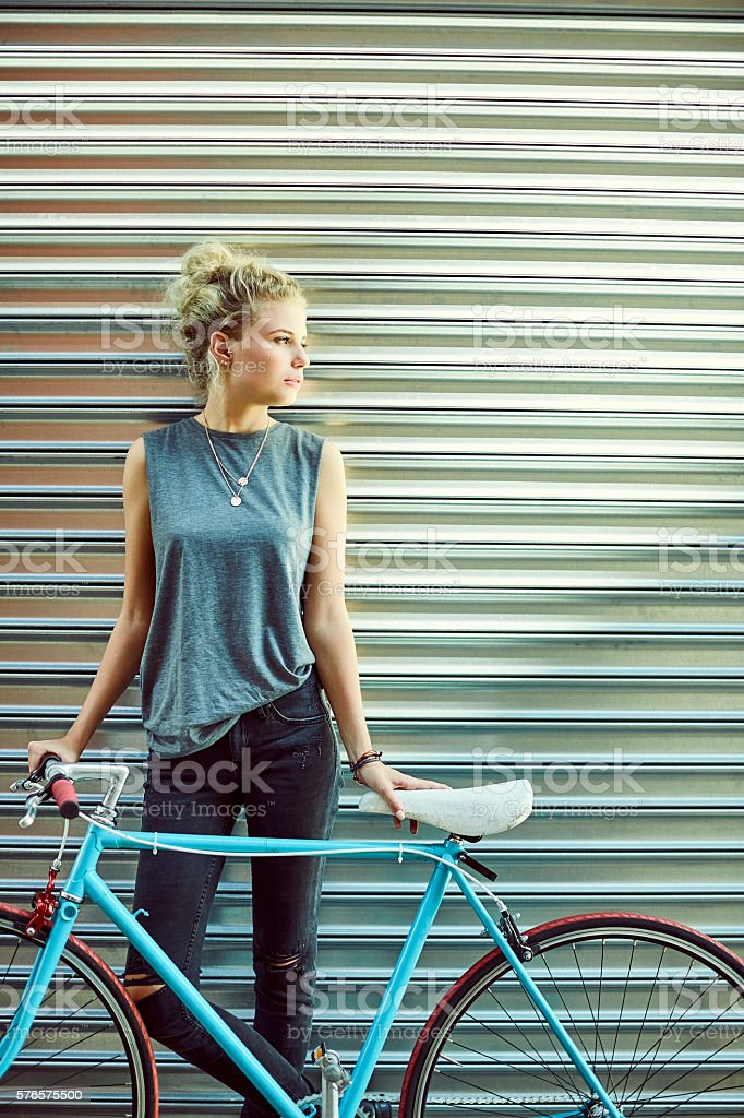 Thoughtful woman with bicycle against shutter stock photo