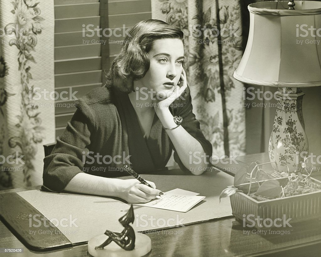 Thoughtful woman writing letter at desk, (B&W) stock photo