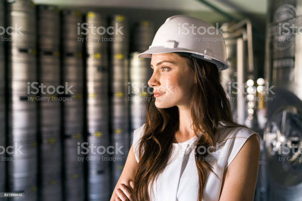 Thoughtful worker wearing hardhat in brewery stock photo