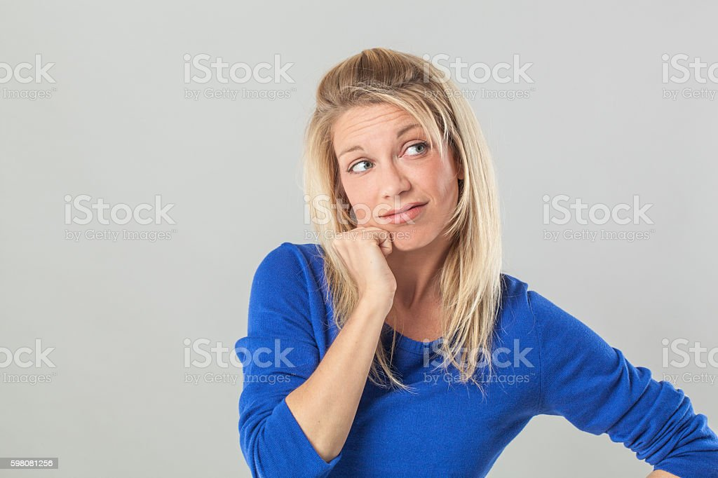 thoughtful young blond woman daydreaming, looking away from mistake stock photo