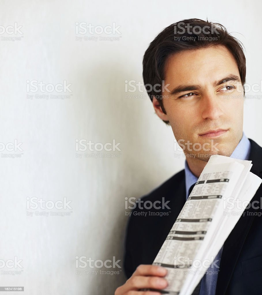 Thoughtful young business man holding a newspaper royalty-free stock photo