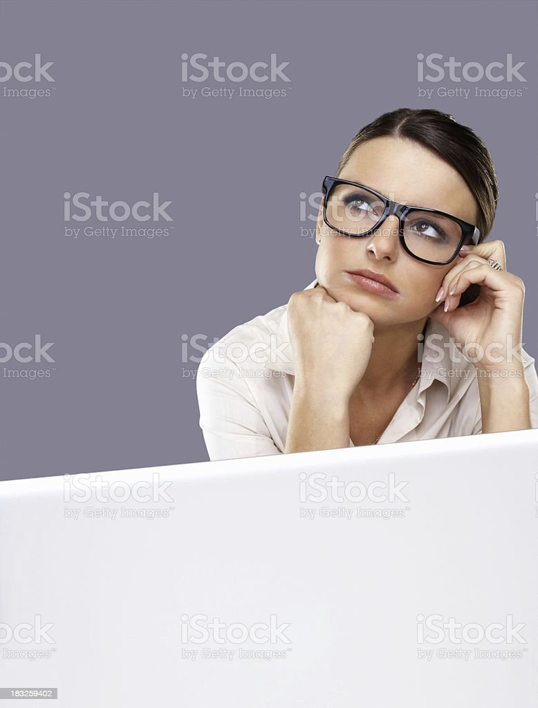 Thoughtful young business woman wearing spectacles with laptop royalty-free stock photo