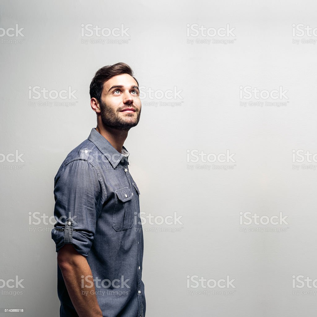 Thoughtful young businessman against grey background stock photo