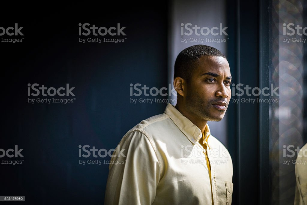 Thoughtful young businessman at creative office stock photo