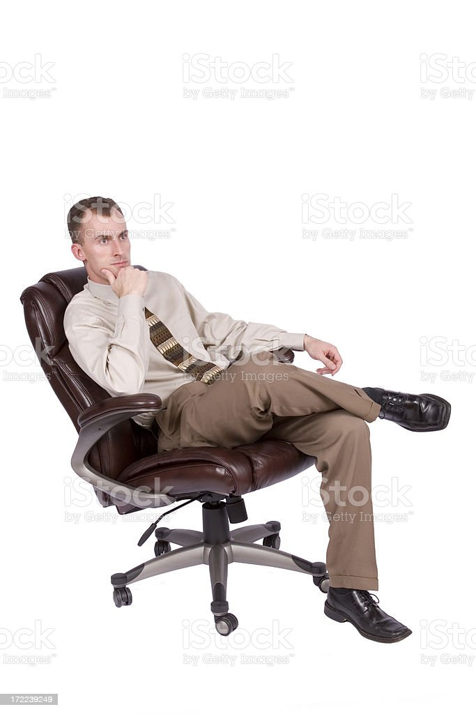 Thoughtful young businessman sitting in office chair royalty-free stock photo