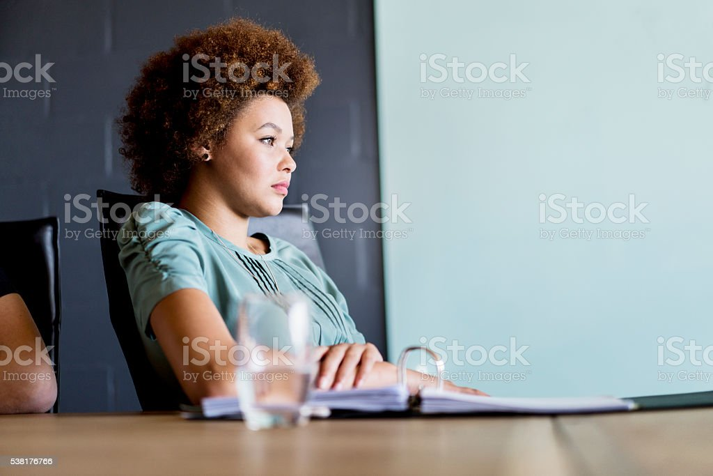 Thoughtful young businesswoman in board room stock photo