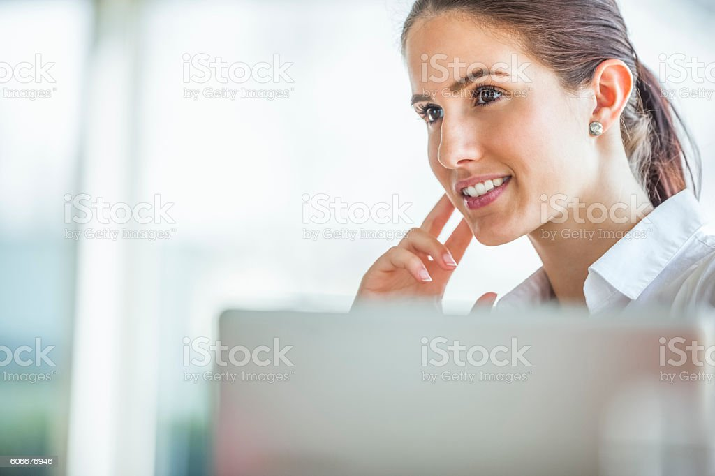 Thoughtful young businesswoman looking away in office stock photo