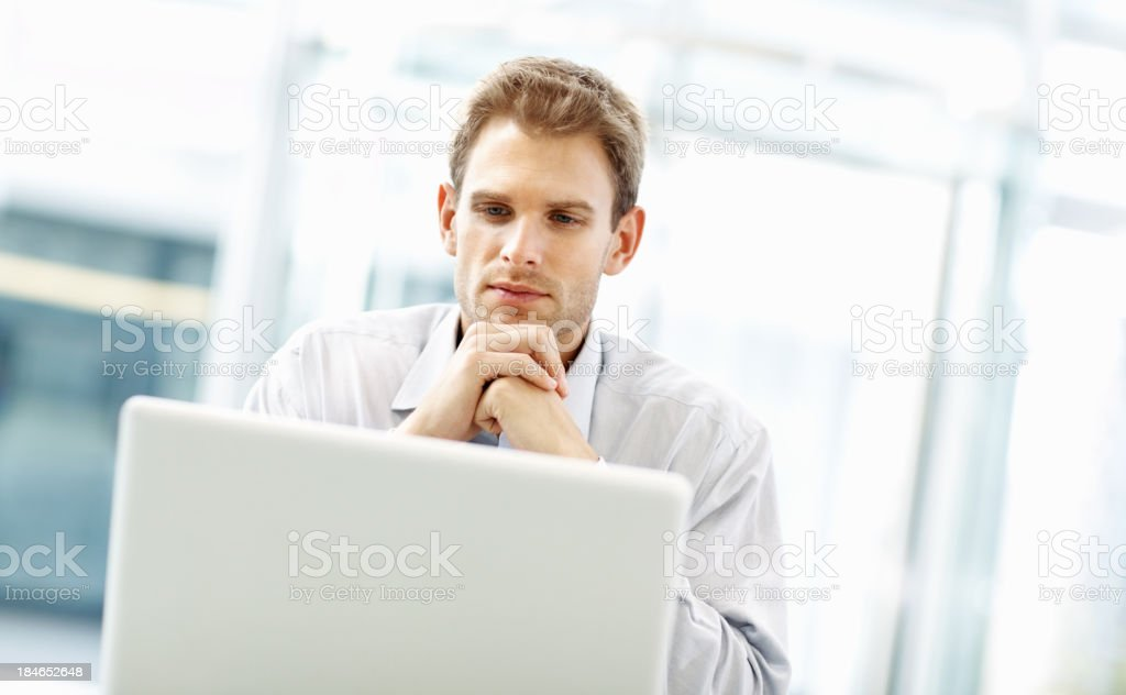 Thoughtful young executive using his laptop royalty-free stock photo