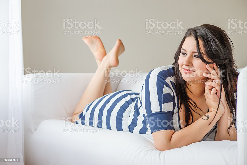 Thoughtful young fashion model dreaming on sofa stock photo