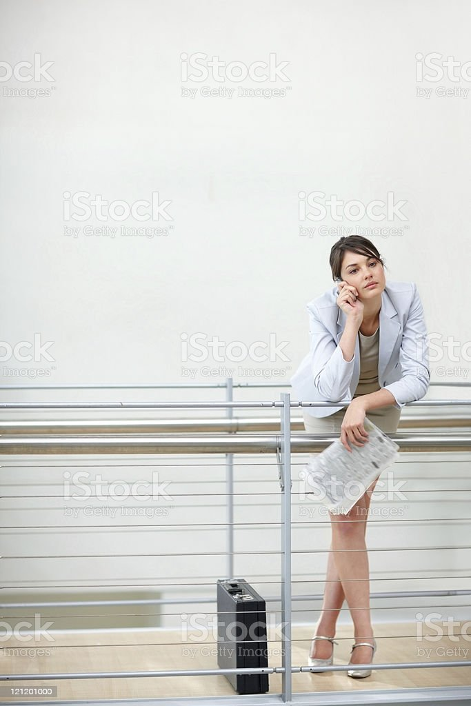 Thoughtful young female executive using cellphone by railing at office royalty-free stock photo
