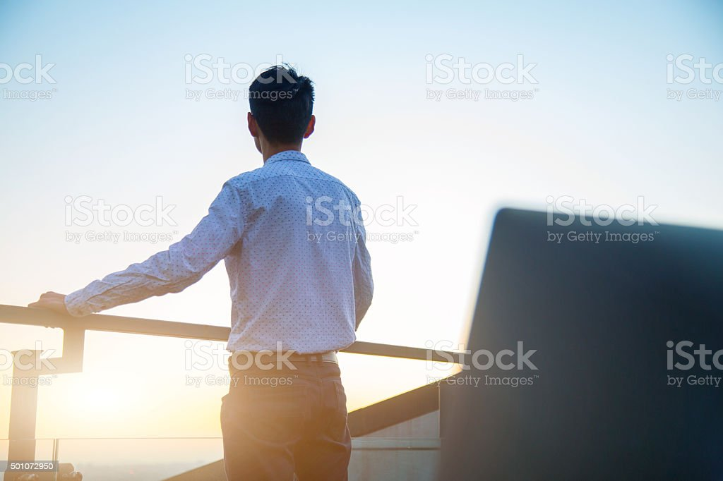 Thoughtful Young Professional Overlooking Downtown at Sunset stock photo