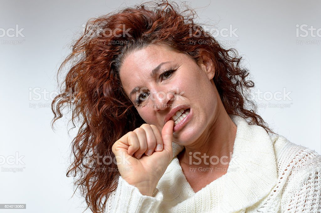 Thoughtful young woman chewing her thumb nail stock photo