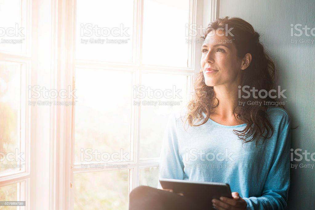 A photo of thoughtful woman sitting on window sill. Young female is...