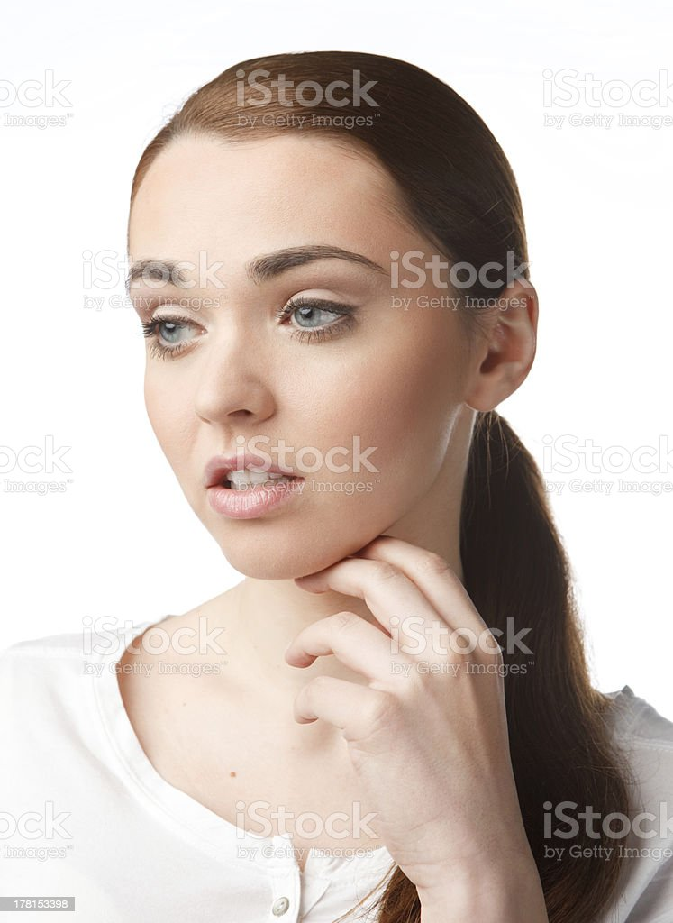 Thoughtful young woman holding hand on chin, staring into space royalty-free stock photo