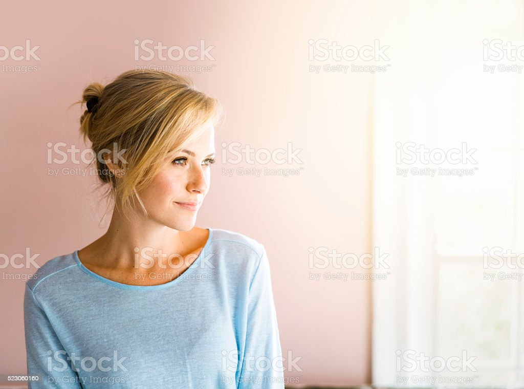 Thoughtful young woman in brightly lit home stock photo
