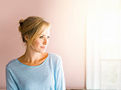 Thoughtful young woman in brightly lit home