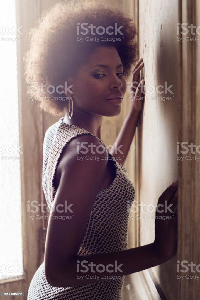 Thoughtful young woman leaning on door at home, Havana, Cuba stock photo