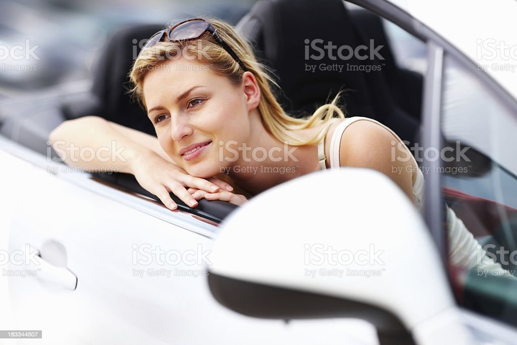 Thoughtful, young woman resting at car door royalty-free stock photo