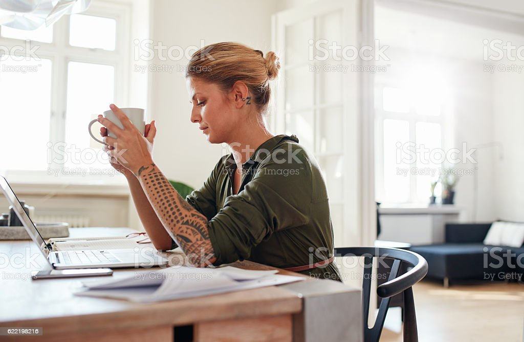 Thoughtful young woman with coffee sitting at table stock photo