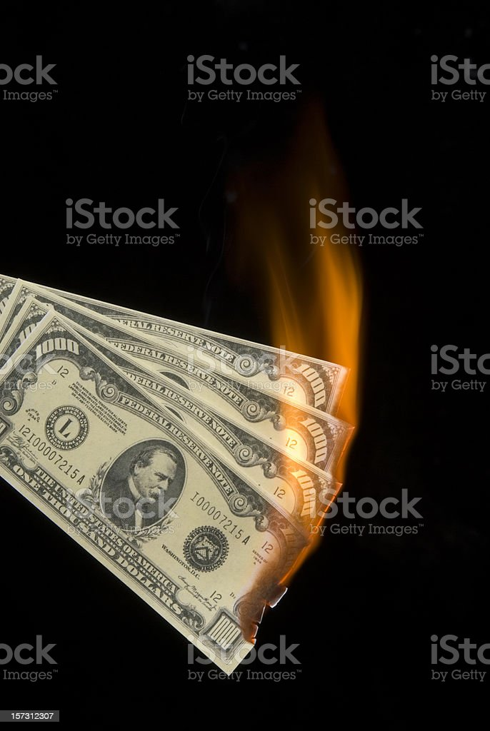 Thousand dollar bills on fire/isolated on black-money to burn stock photo
