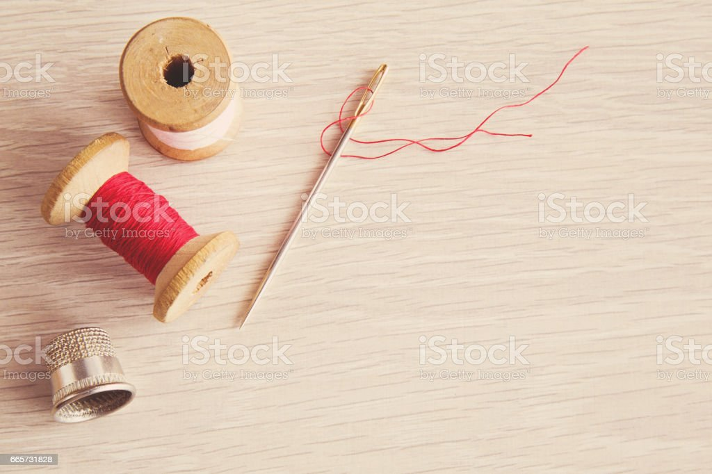 Thread, needle and iron thimble on the wooden table. Sewing works. Handmade. Womanly hobby. stock photo