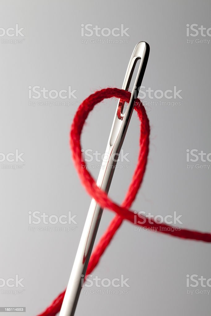 Thread through the needle eye stock photo