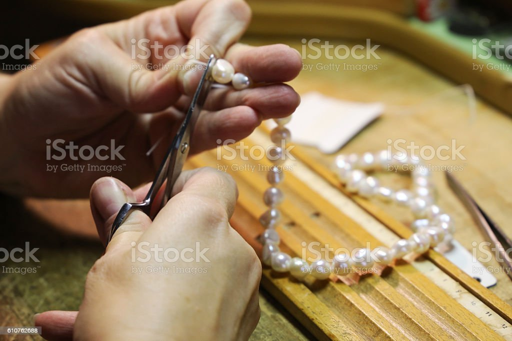 Threading a pearl necklace stock photo