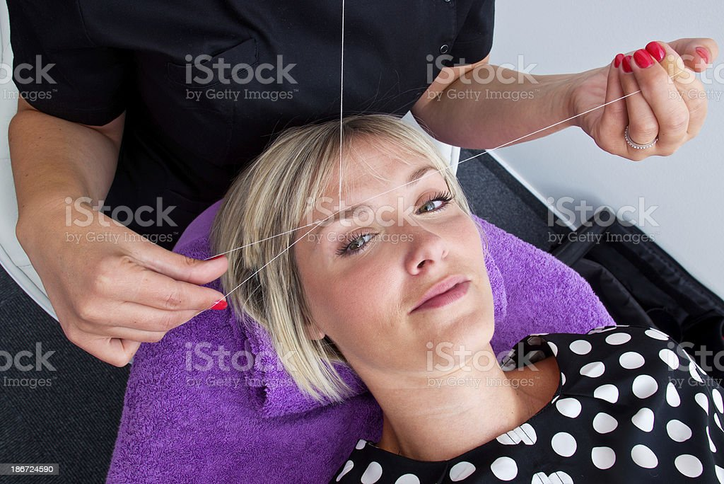threading hair removal stock photo