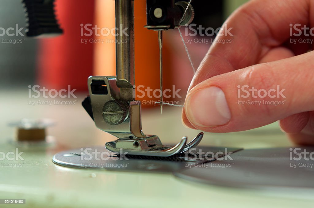 Threading the needle in a sewing machine stock photo