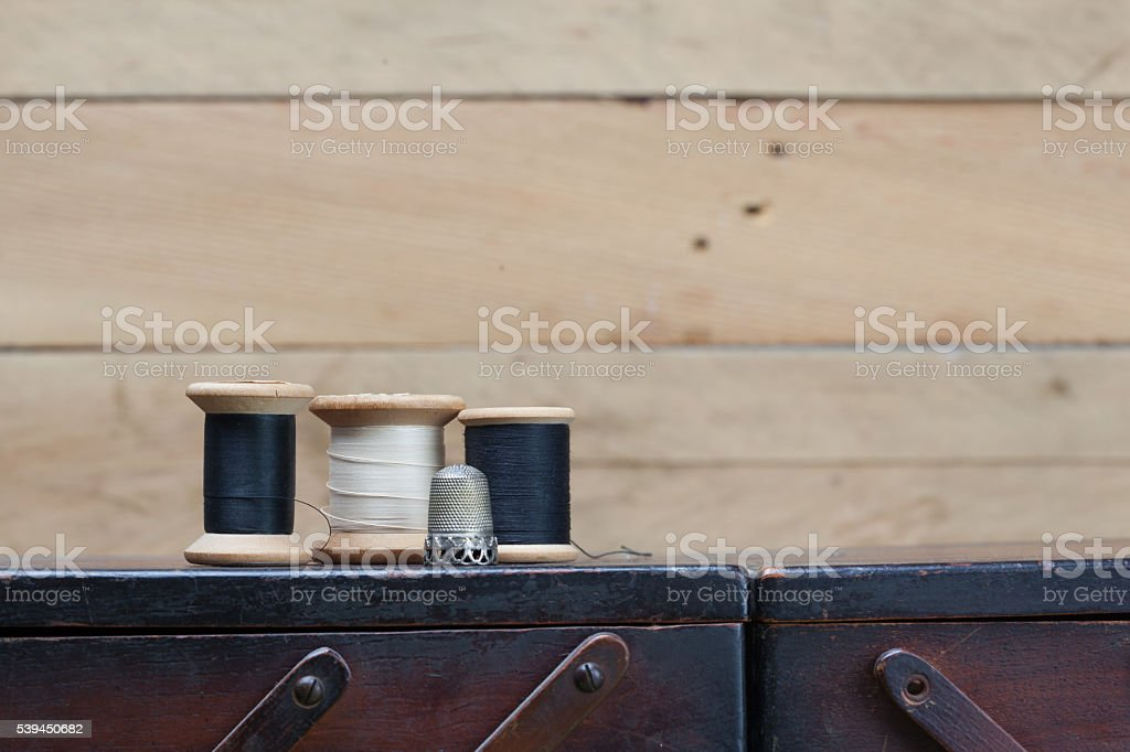 Threads and needlework tools on top of wooden container stock photo