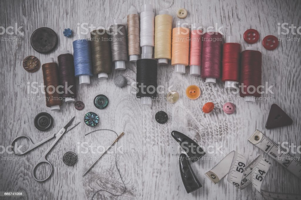 Threads, needle, scissors and buttons - basic accessories starting sewing. Sewing works. Handmade. stock photo