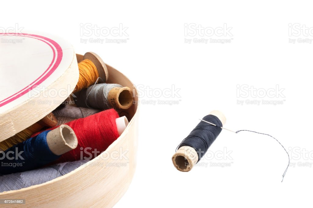 threads of different colors in a wooden box on a white background stock photo
