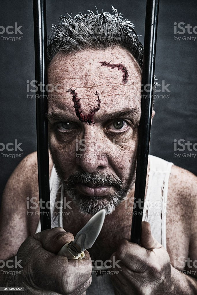Threatening crazy white man in jail with shiv stock photo