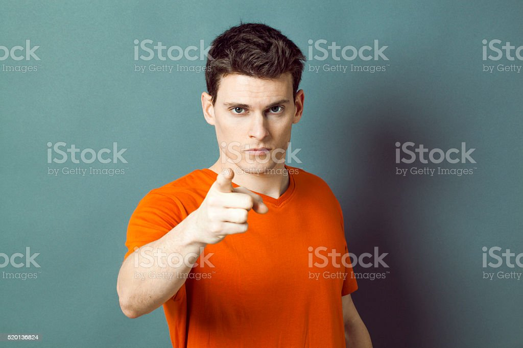 threatening handsome young man showing something or someone with index stock photo