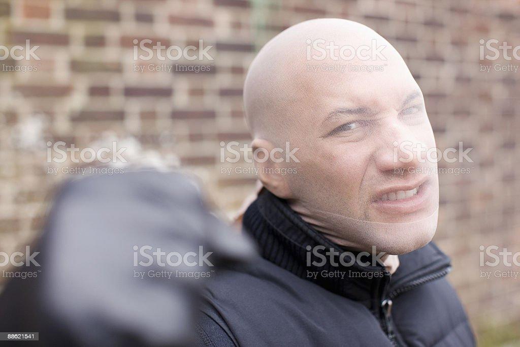 Threatening mugger with stocking mask stock photo