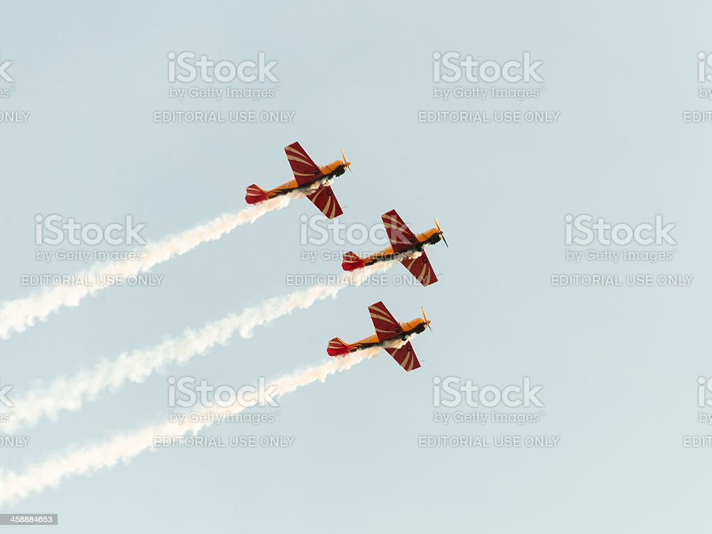 Three 3 Yak-52 aircrafts fly against blue sky background royalty-free stock photo