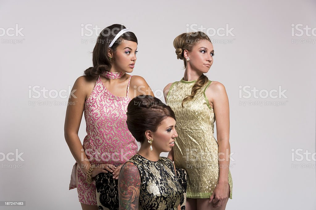 Three 60s styled women looking viewer's right. royalty-free stock photo