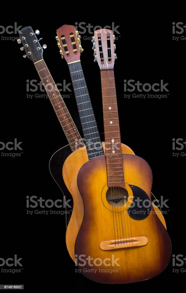 Three acoustic guitars on black background stock photo