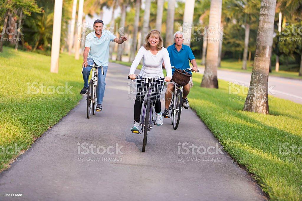 Three active seniors take a bicycle ride stock photo