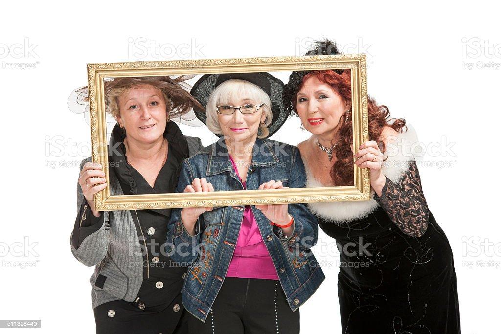 Three adult ladies laugh in the studio stock photo