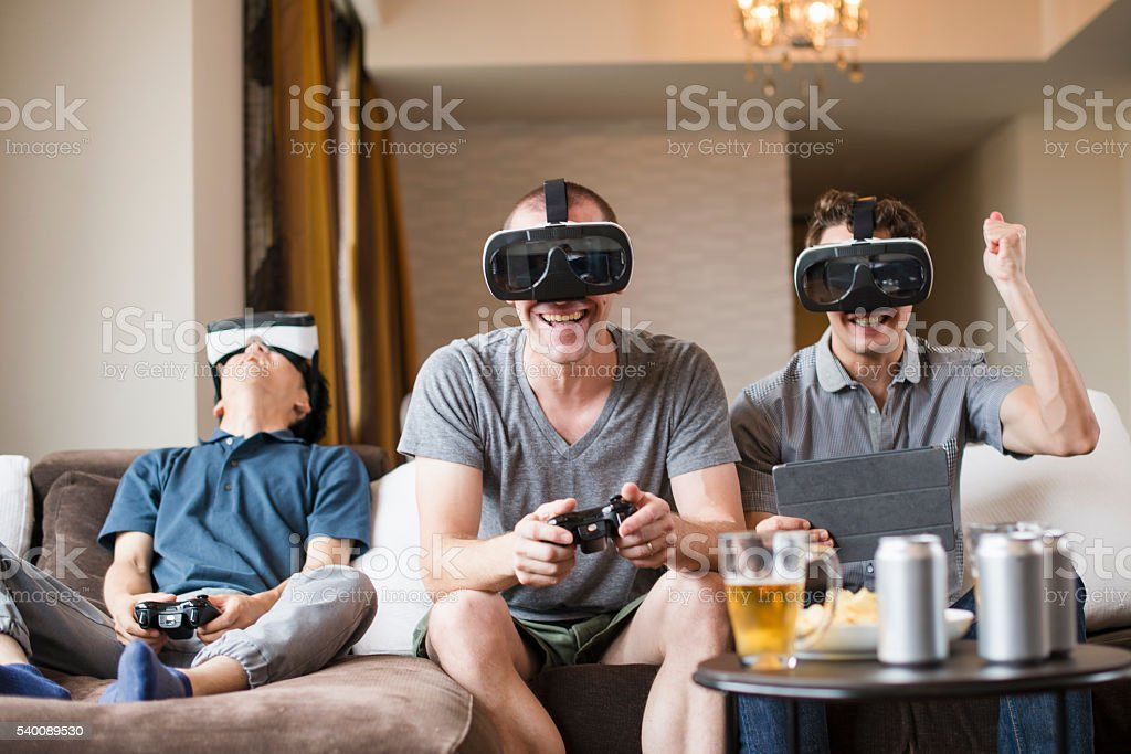 Three adults to play with a virtual reality headset stock photo