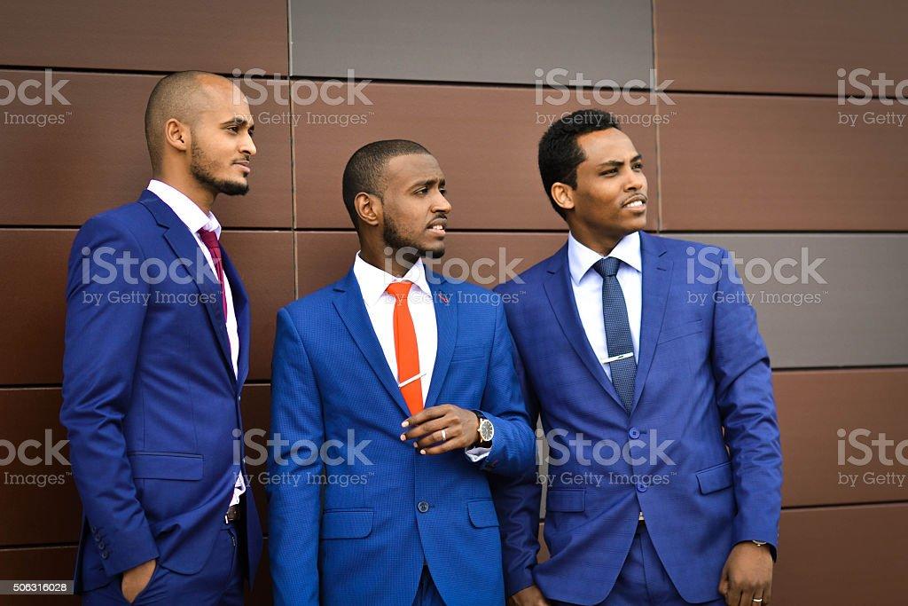 Three African, Azerbaijani, Uzbek foreigners. Successful businessmen discuss buildings stock photo