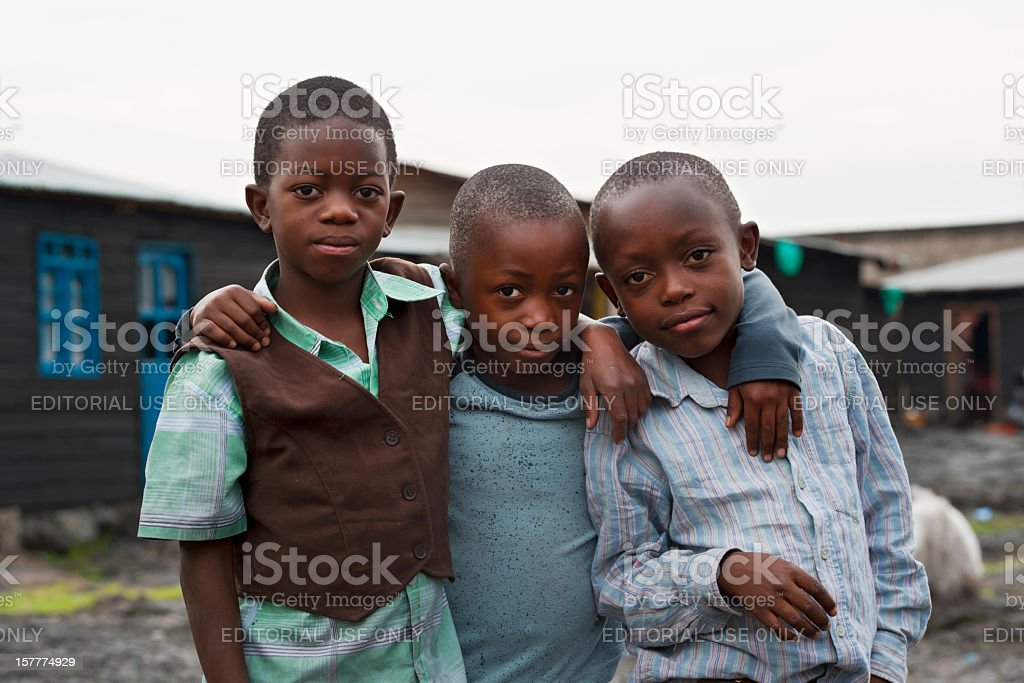 Three african boys in the destroyed town of Goma, Congo stock photo