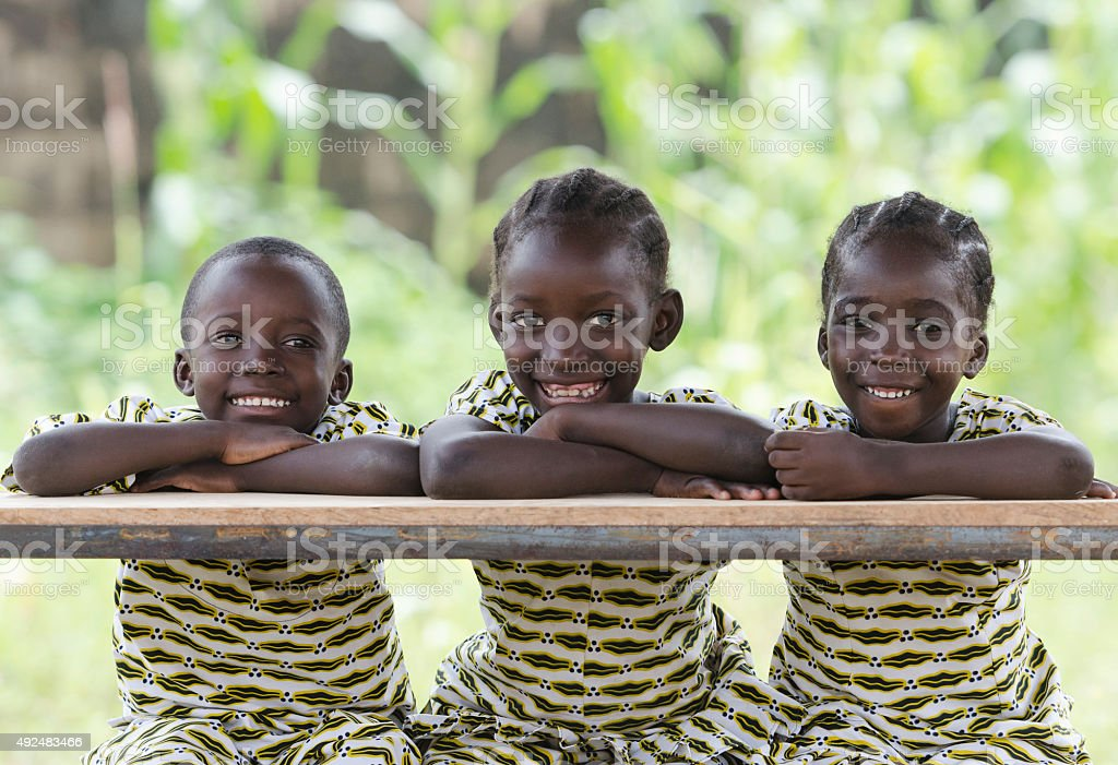 Three African Children at School Education Symbol Schoolgirl Schoolboy Sitting stock photo