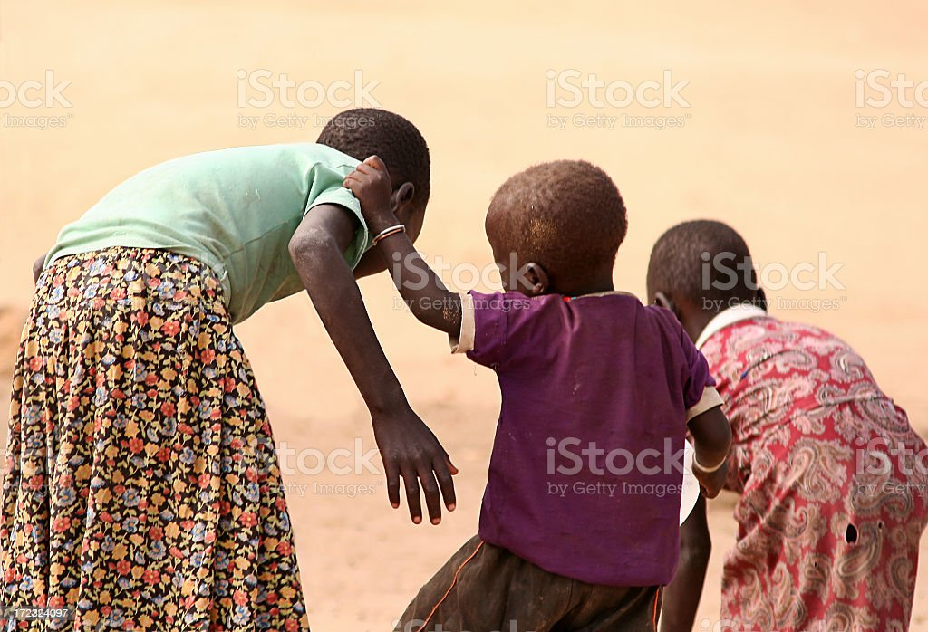 Three African children helping each other in the desert stock photo
