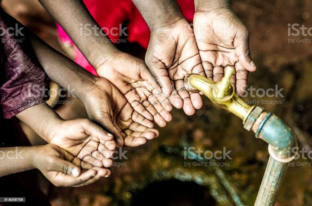 Three African Children Holding Their Hands Cupped under Water Tap stock photo