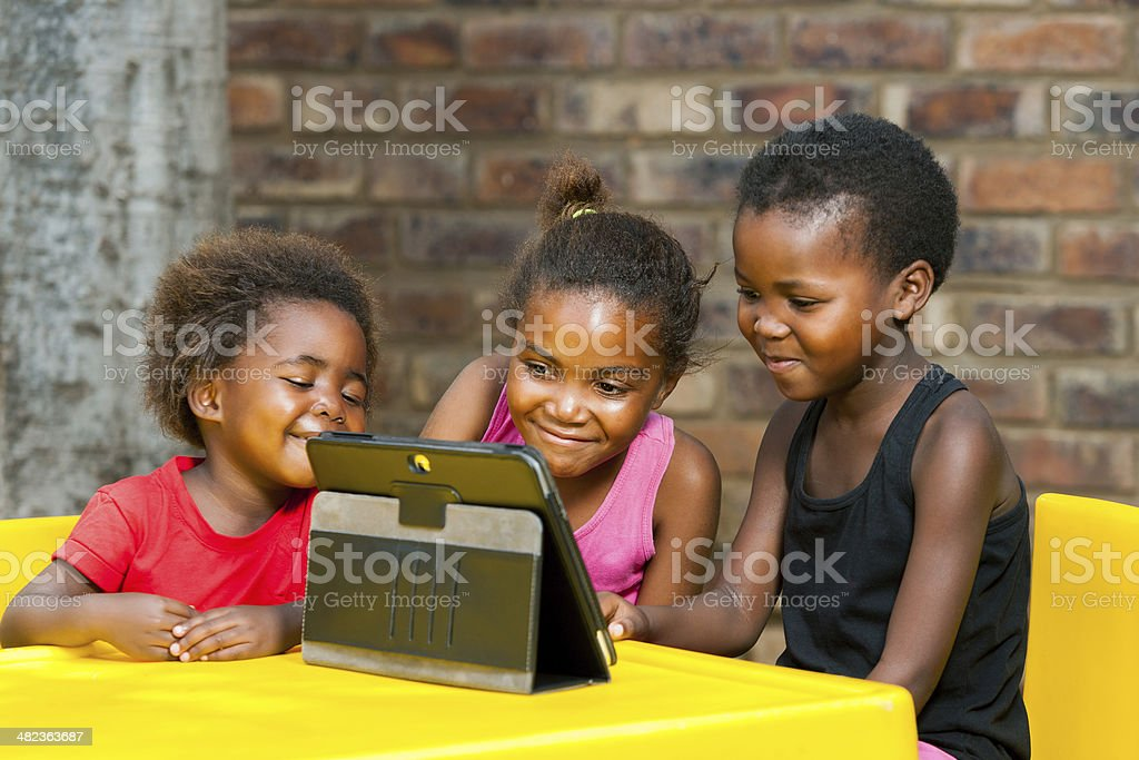 Three african kids playing together on tablet. stock photo