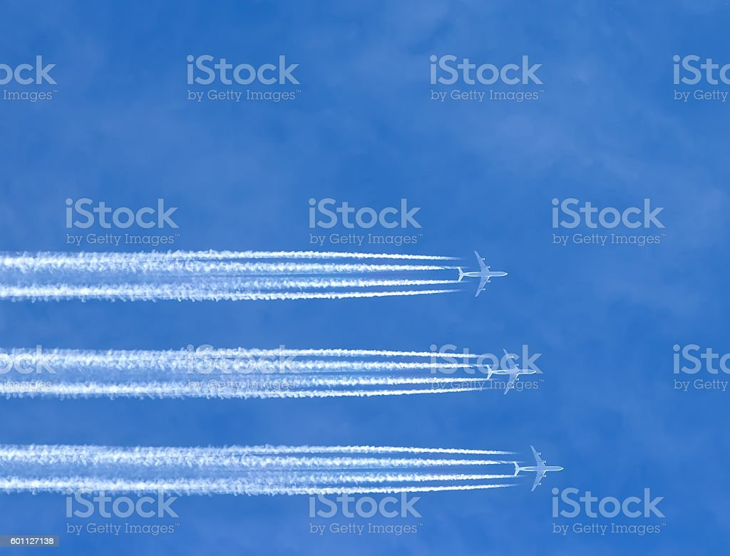 three airplanes leaving horizontal traces on clear blue sky. stock photo
