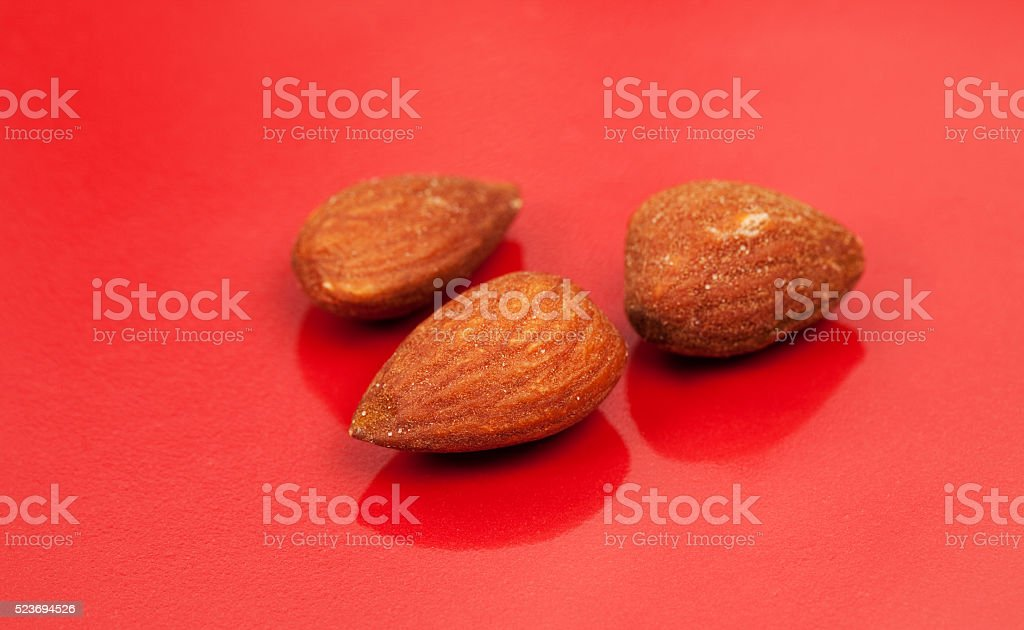 Three Almonds on Red Background stock photo